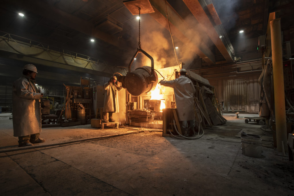 Three employees working with metal in the foundry.
