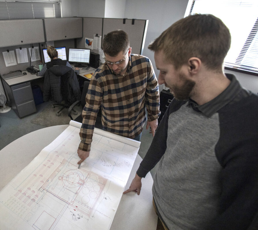 Two employees working on an engineering diagram.